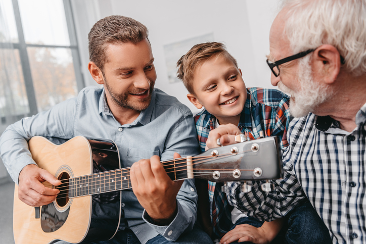 three generations playing guitar